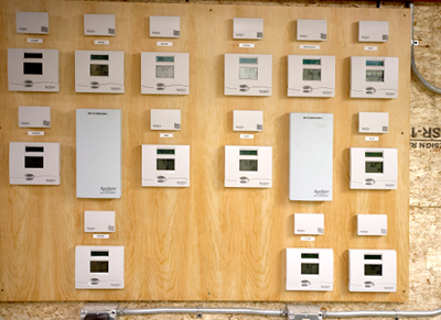 Thermostats are mounted in the mechanical room and connected to  innocuous temperature sensors throughout the house